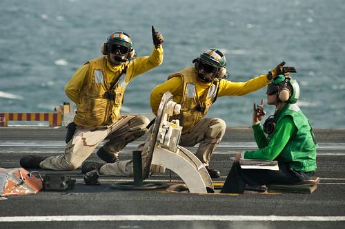 Sailors signal the launch of an F/A-18F Super Hornet.