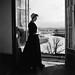 Peg Bartlett in 100 year old period dress looking out top window, Aberglasslyn House, Aberglasslyn, NSW, Australia - March 24, 1961