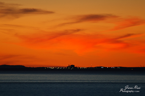 A sunset at sea over the lights of the port.