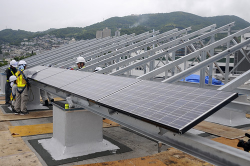 Japanese contractors install solar panels on the Public Works building roof at Fleet Activities Sasebo, Japan.
