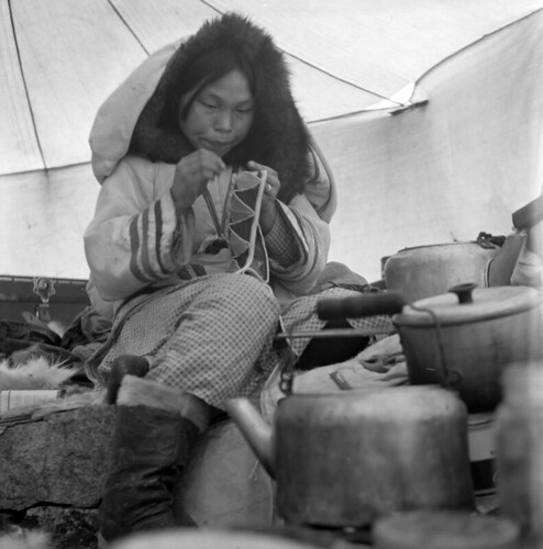 A woman sitting inside of a tent focusing on her sewing project