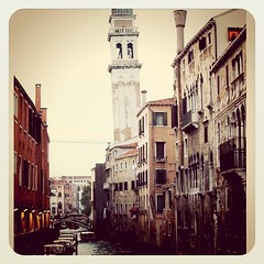 A quiet canal in Venice with a creaky bell tower defying logic that it remains upright...