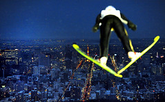 A competitor takes part in an official training session of the World Cup Ski Jumping competition as the lights of the city of Sapporo twinkle in the background, by Kazuhiro Nogi