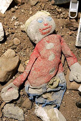 Ash-covered rag doll lies in debris from the World Trade Center site, by Kathy Willens