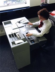 Woman using cheque encoding machine - 1990s