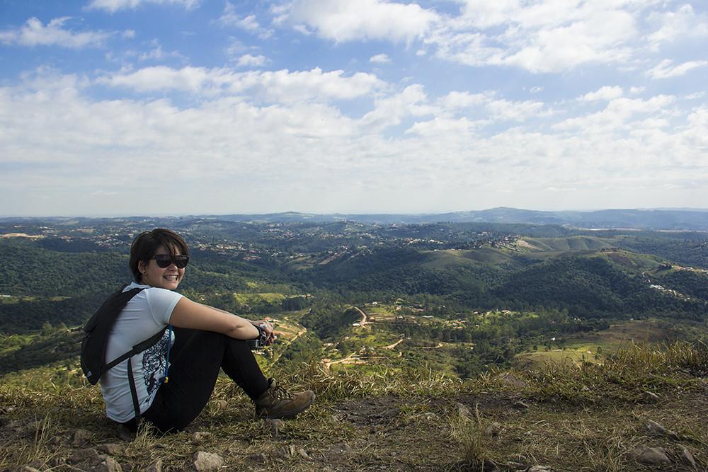 Trilha Morro do Sabóo - Carolina Kina em cima do morro com vista da cidade para baixo