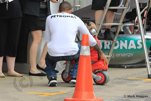 Lewis Hamilton gives a child a tour of his pit garage at the 2013 Spanish Grand Prix
