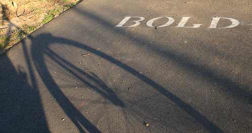 "Shadow of bike and stenciled word ""BOLD"""