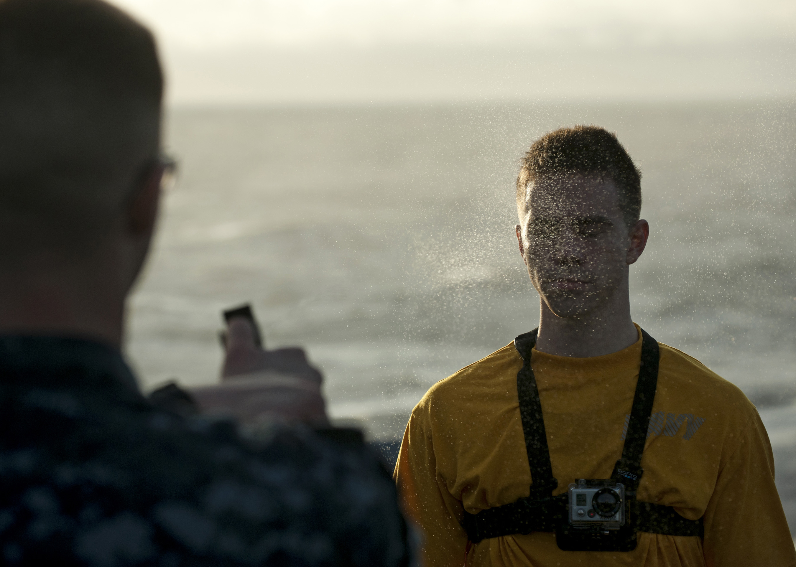 A sailor is sprayed in the face with liquid fire.