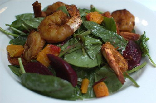 Roast beetroot, pumpkin, spinach, goats' feta and baked tomatoes salad with harissa king prawns