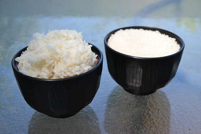 Compose a photograph that includes a 'finished product' and at least one of its 'raw materials'. Cooked rice & Uncooked rice