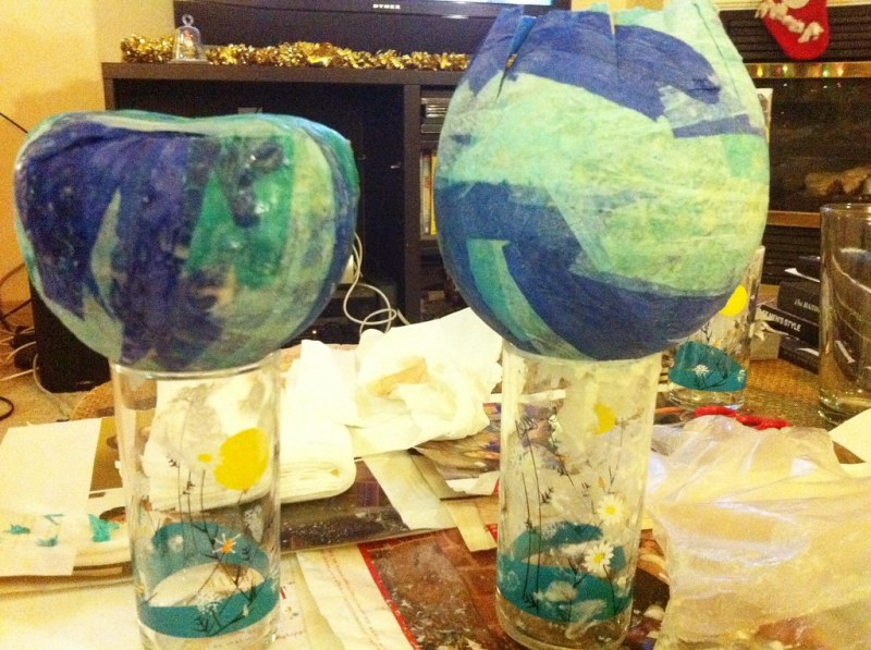 Paper mâché the open end of the ball flat, as flat as you can, so it will sit on a table easily