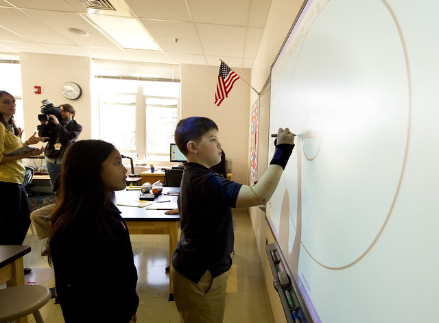 children drawing on interactive whiteboard