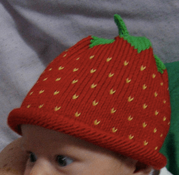 Photo of baby wearing a hat that looks like a strawberry