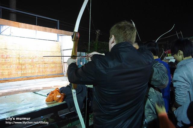 尼第一次玩射箭,不過他連怎麼把箭放上去都有問題,後來老闆出手相救指導了一下。