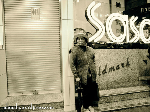well dressed lady with hat by a SaSa sign