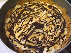 Drizzle of chocolate over banana slices and digestive biscuit crust