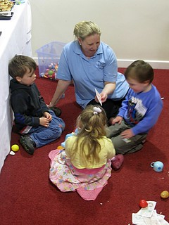 A nanny playing with three children
