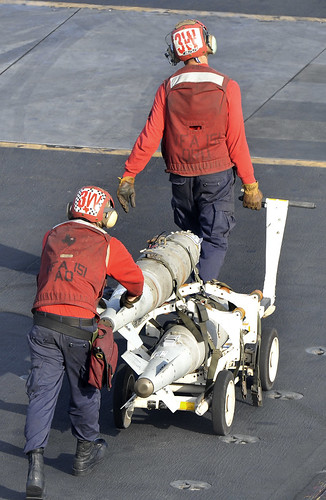 Sailors move ordnance on the flight deck of USS Abraham Lincoln. by Official U.S. Navy Imagery