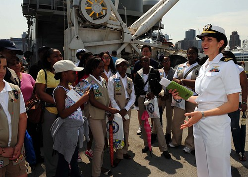 A Navy officer speaks to Girl Scouts from the Greater Area of New York City during a tour of the ship for Fleet Week New York 2012. by Official U.S. Navy Imagery