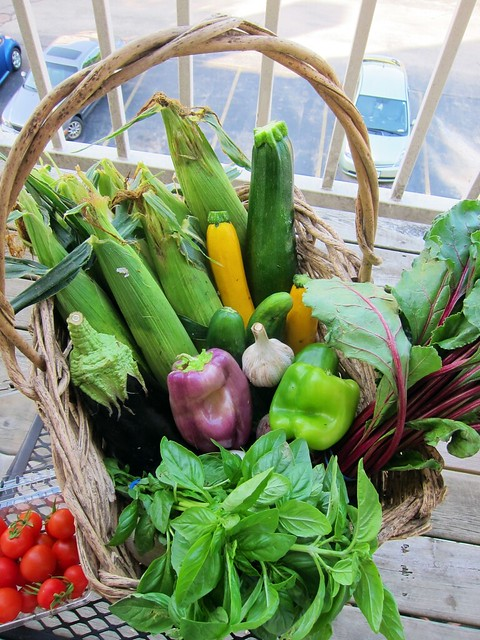A big ol' basket of veggies - sweet corn and basil feature prominently among them.