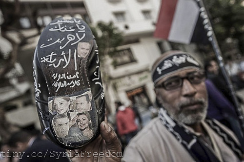 An Egytpian man holds a shoe with pictures on its sole depicting Syrian President Bashar al-Assad (C-R), US President Barack Obama (bottom-L),  Hillary Clinton and Israeli Premier Benjamin Netanyau