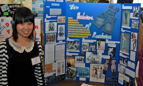 A student poses next to her blue poster on the influence of denim jeans.