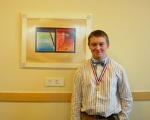 Gareth Robinson poses with his artwork on the wall of a committee room in the Maine State House.