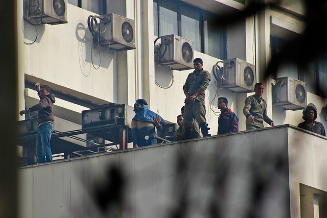 Army Soldier with a dirty gesture on top the Parliament building