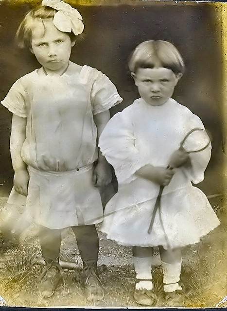 Both children are frowning wearing dresses while Hollis clutches a whip