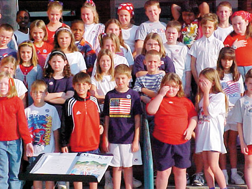 Group of singing school children some crying.  Aaron in center in blue shirt with American Flag prominently displayed on it
