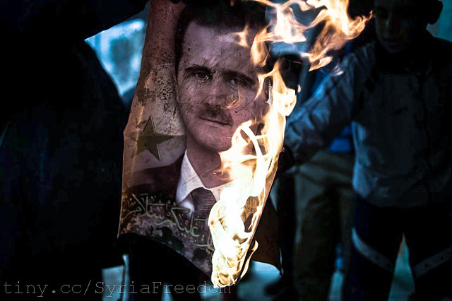 A member of the Free Syrian Army burns a portrait of Bashar Assad in Al Qsair. Jan. 25, 2012