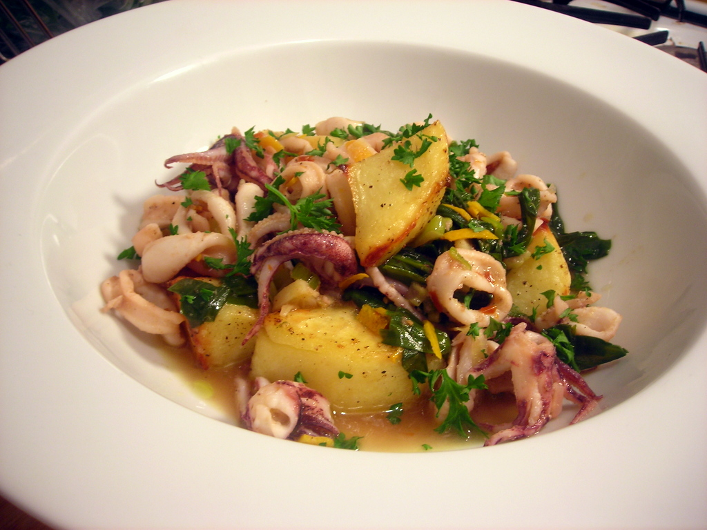 Olive oil-poached squid with orange peel, garlic and ramps, and crispy roasted potatoes