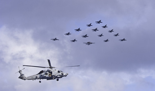 A helicopter flies over tiger cruise families during an air power demonstration. by Official U.S. Navy Imagery