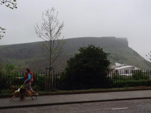 Beth and Annie striding along with Arthur's Seat and Scottish Parliament in the background