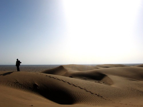 Silhouette of a walker atop sand dune in the Wahiba