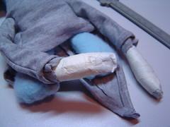 Mãos enfaixadas após atravessar as mangas da túnica.