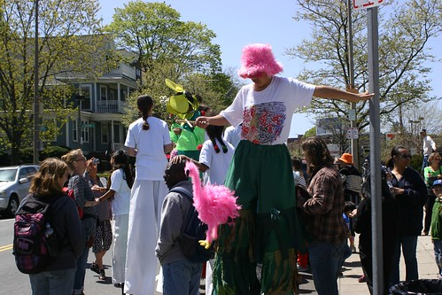 Stilt walker boy practices with pink flamingo puppet
