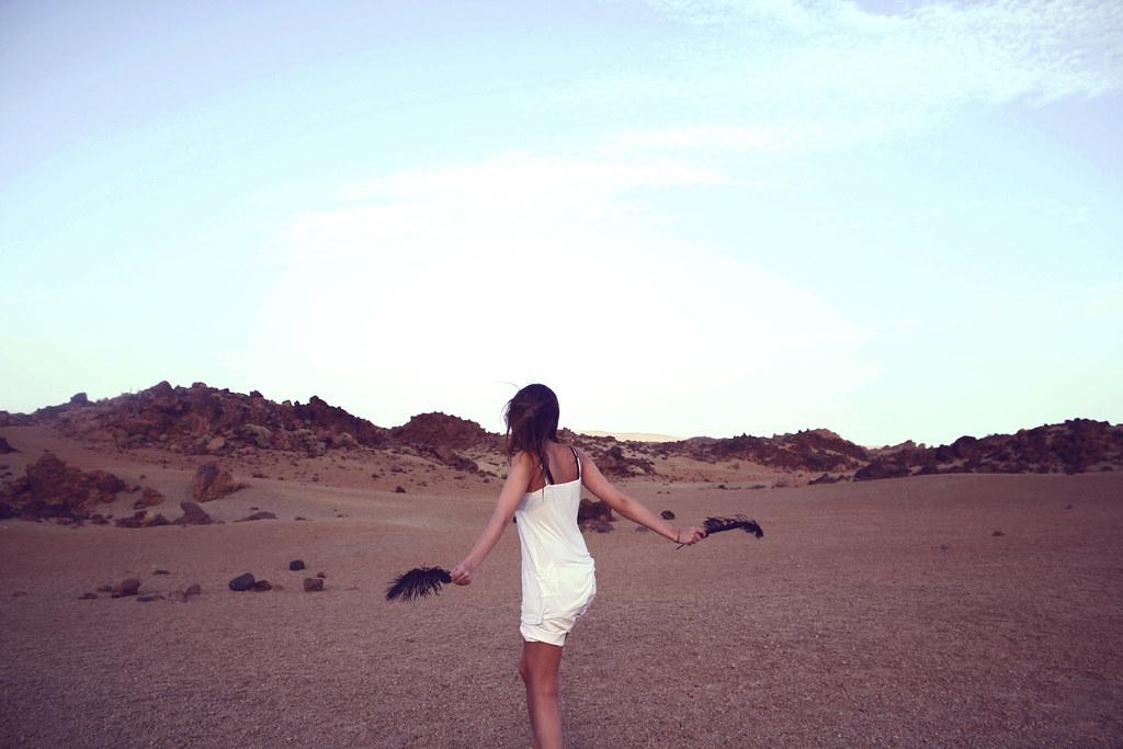 Imagen gratis de una chica en un desierto con plumas en las manos