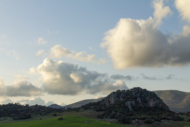 Puffy clouds with grass & craggy rocks