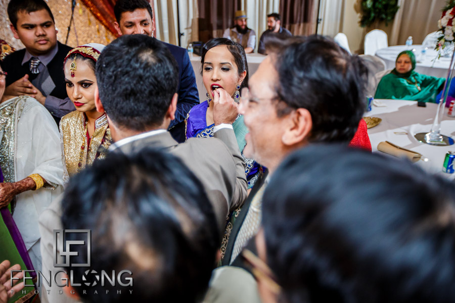 Indian bride and groom cutting cake during wedding reception