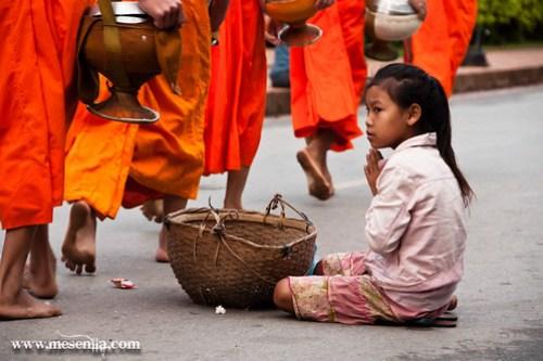 Nena esperant l'excedent dels monjos de Luang Prabang