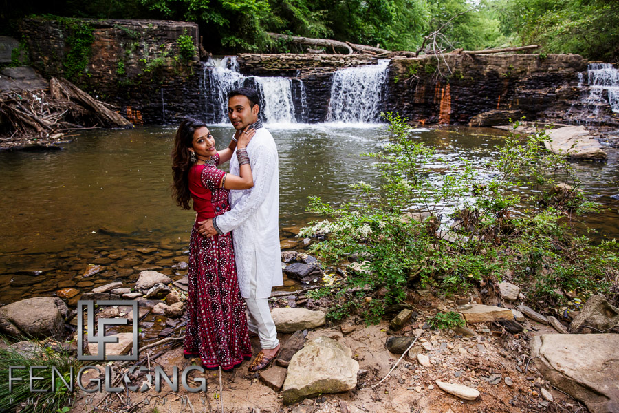 Indian bride and groom in front of waterfall in romantic Bollywood pose