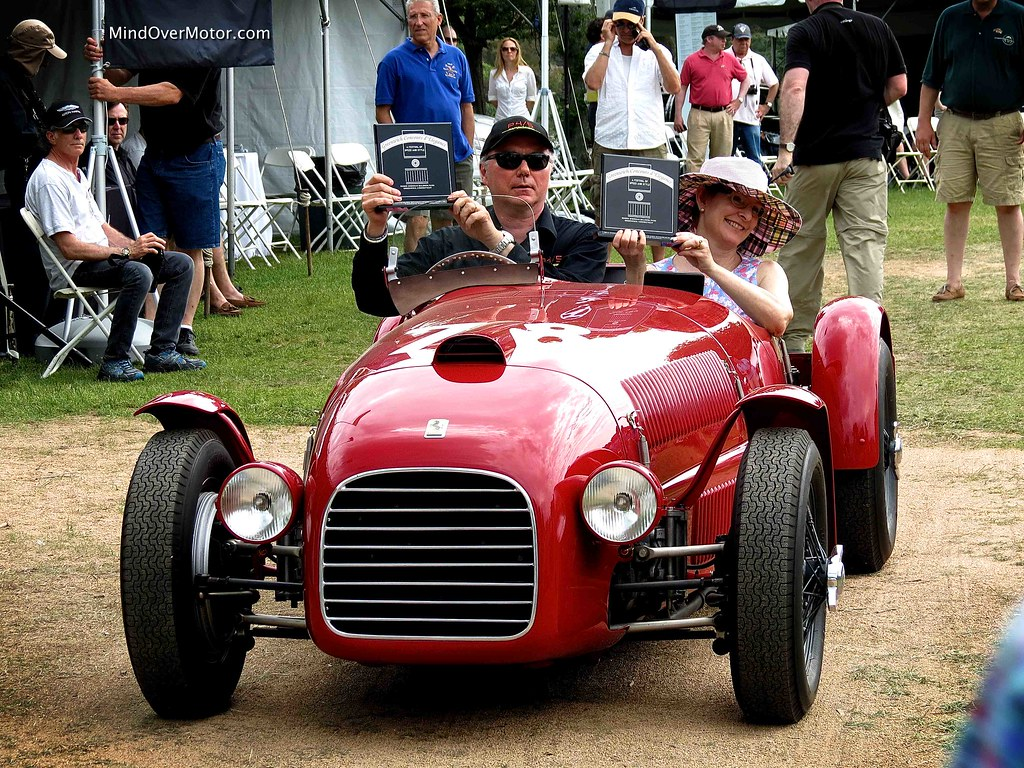 James Glickenhaus in his 1947 Ferrari 159S Spyder Corsa, holding up his award for Best In Show