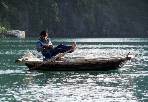 Small boat being rowed with the rower's feet in Halong Bay