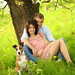 young and happy couple is sitting on a meadow with a dog