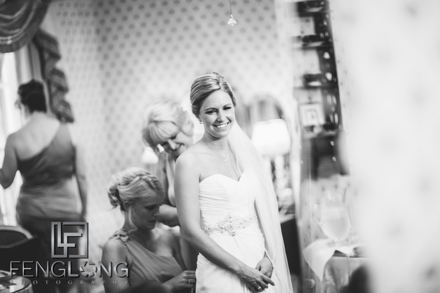 Bride putting on her wedding dress in black and white