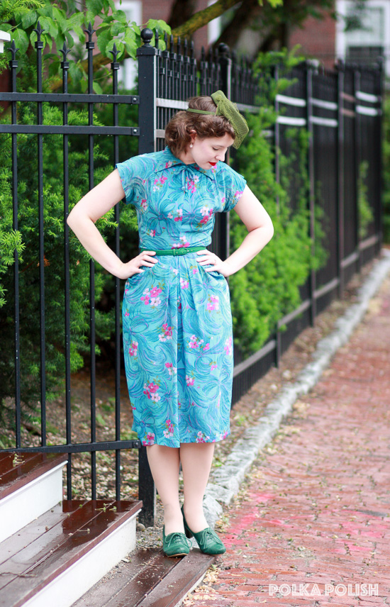 A 1940s look featuring a floral rayon dress in shades of teal, olive, and bright pink paired with green accessories