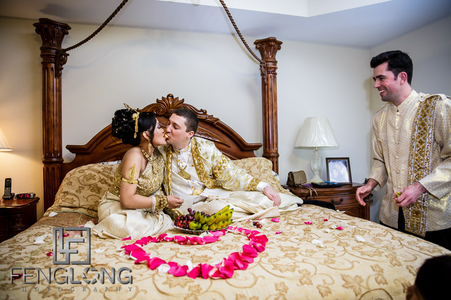 Cambodian bride and American groom feeding each other during Cambodian wedding ceremony