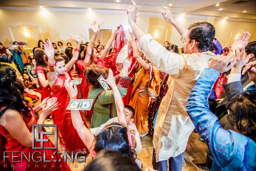 Guests throw money on the bride during her entrance at a Pakistani & Bengali Muslim wedding